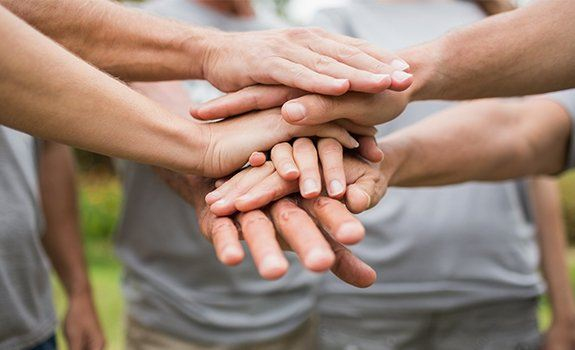People in a circle with their hands together in the center