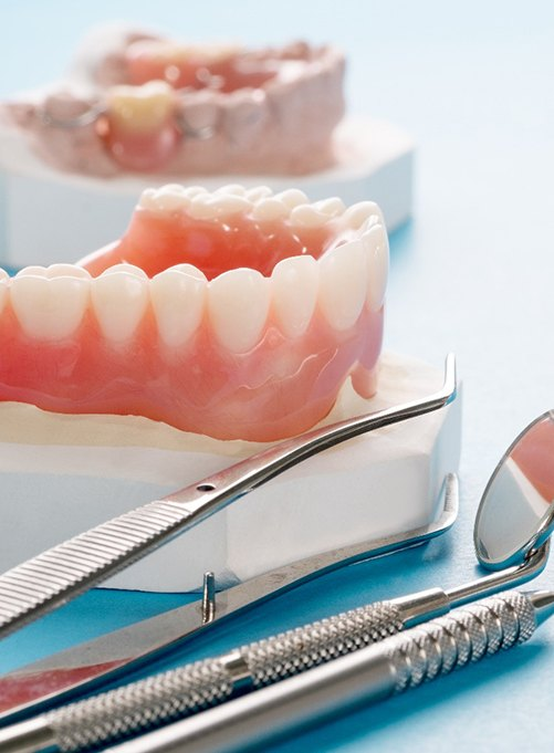 Closeup of dentures in Rockwall and dental tools