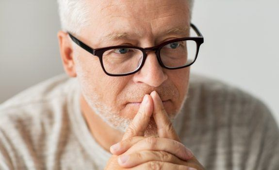 Older man contemplating dental implant tooth replacement