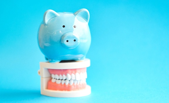 Piggy bank atop model teeth representing the cost of Invisalign in Rockwall