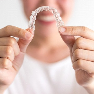 Woman in background holding up Invisalign in Rockwall