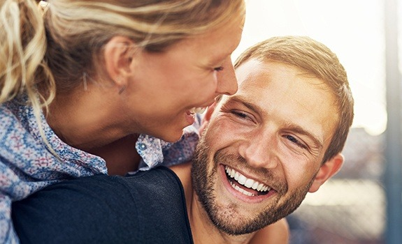 Smiling man and woman with natural looking dental crowns