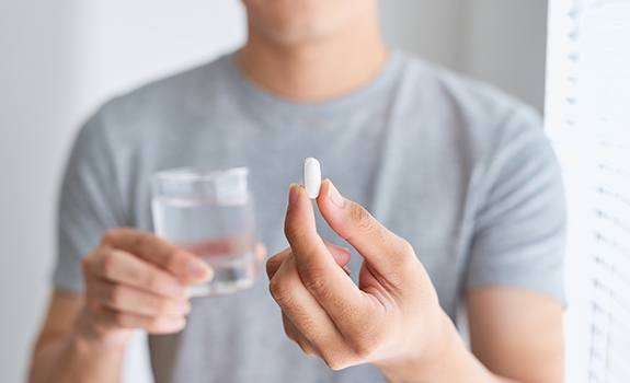 Patient holding a glass of water and oral conscious dental sedation pill