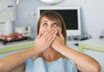 Fearful woman in need of sedation dentistry covering mouth